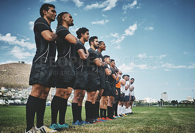 Buy stock photo Shot of a team of confident young rugby players standing at attention singing their anthem outside on a field before a rugby match