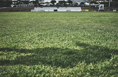 Buy stock photo Low angle shot of an unrecognizable person's shadow being cast on a rugby field outside during the day