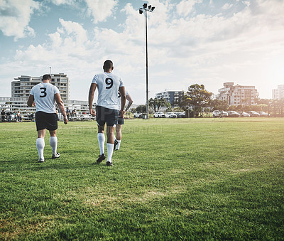Buy stock photo Shot of a group of young rugby players walking off the filed after the match outside during the day