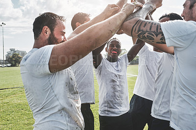 Buy stock photo Cropped shot of a group of cheerful young rugby players celebrating their win after a match outside during the day