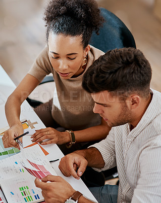Buy stock photo Shot of a young businessman and businesswoman working together on a task in a modern office