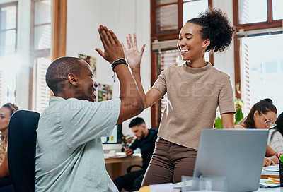 Buy stock photo Shot of a young businessman and businesswoman giving each other a high five while using a laptop in an office