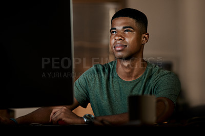 Buy stock photo Shot of a young businessman using a computer in a modern office at night