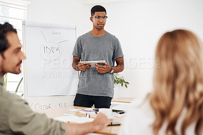 Buy stock photo Shot of a young businessman using a digital tablet while giving a presentation in an office