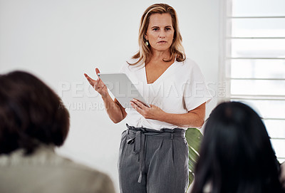 Buy stock photo Shot of a mature businesswoman using a digital tablet while speaking at a conference