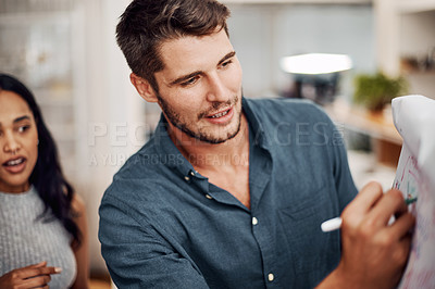 Buy stock photo Cropped shot of a handsome young businessman using a visual aid to brainstorm with his colleagues in the office
