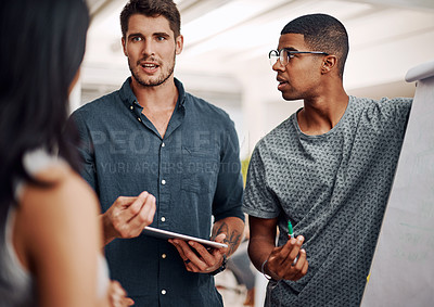 Buy stock photo Cropped shot of a diverse group of businesspeople standing together and using a visual aid to brainstorm in the office
