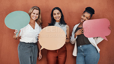 Buy stock photo Cropped portrait of a young group of businesswomen standing together and holding speech bubbles while outside