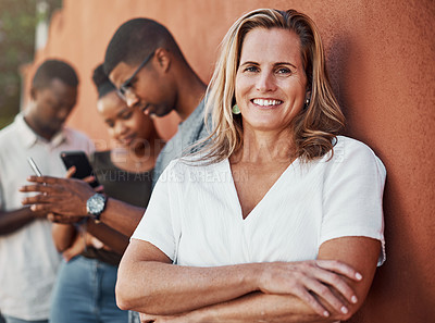 Buy stock photo Cropped portrait of an attractive young businesswoman standing with her colleagues against a wall outside
