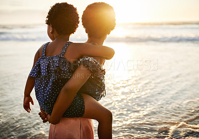 Buy stock photo Shot of a young woman spending time at the beach with her adorable daughter