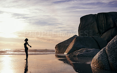 Buy stock photo Full length shot of an attractive young woman stretching and practicing yoga on the beach at sunset
