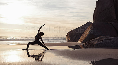 Buy stock photo Full length shot of an athletic young woman stretching and practicing yoga on the beach at sunset