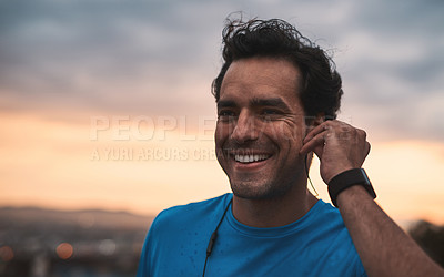 Buy stock photo Shot of a young man using earphones while during a workout in the city at sunset