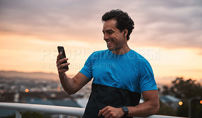 Buy stock photo Shot of a young man using a smartphone during a workout in the city