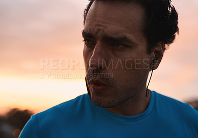 Buy stock photo Shot of a young man going for a run in the city at sunset