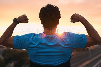 Buy stock photo Shot of a young man flexing his muscles during a workout in the city at sunset