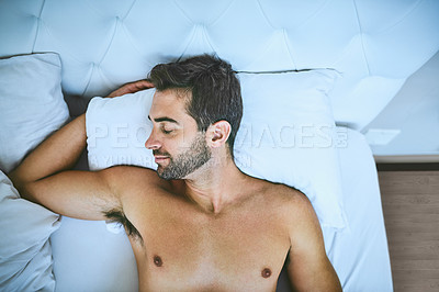 Buy stock photo High angle shot of a handsome young man peacefully sleeping in his bed at home