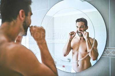 Buy stock photo Cropped shot of a handsome young man looking in the mirror and flossing his teeth in his bathroom at home
