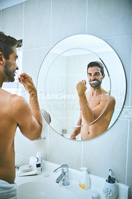 Buy stock photo Cropped shot of a handsome young man brushing his teeth in the bathroom at home