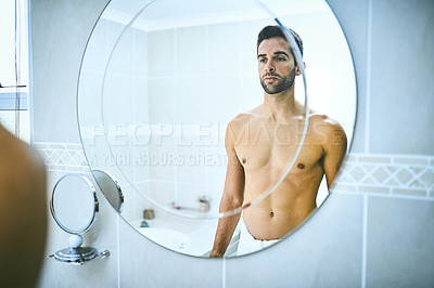 Buy stock photo Cropped shot of a handsome young man looking at himself in the mirror inside his bathroom at home