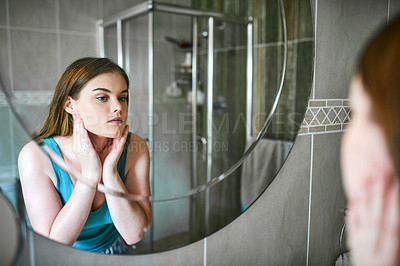 Buy stock photo Cropped shot of a beautiful young woman inspecting her skin in the bathroom at home