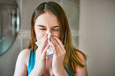 Buy stock photo Shot of a young woman blowing her nose into a tissue while in the bathroom at home
