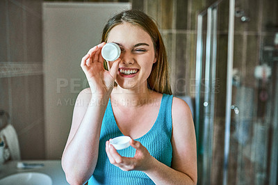 Buy stock photo Shot of a woman holding a pot of moisturizer while going through her morning routine