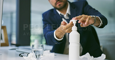 Buy stock photo Shot of a businessman using hand sanitiser while suffering from flu at his work desk