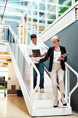 Buy stock photo Shot of two businesspeople walking down a staircase together in an office