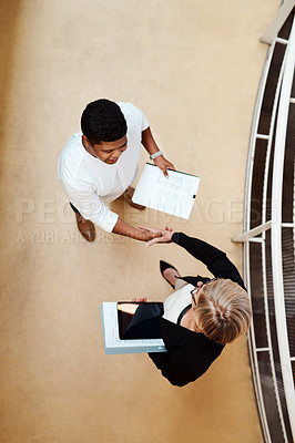 Buy stock photo High angle shot of two businesspeople shaking hands in an office