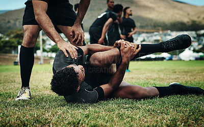 Buy stock photo Cropped shot of a handsome young rugby player suffering with an injury on the field