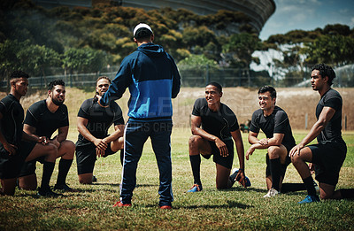 Buy stock photo Cropped shot of a team of rugby players training with their coach on the field during the day