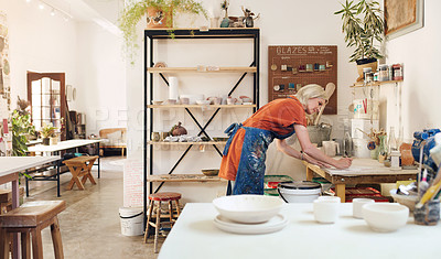Buy stock photo Shot of a mature woman filling out paperwork while working in a pottery studio