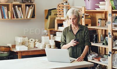 Buy stock photo Shot of a mature woman using a cellphone and laptop while working in a pottery studio