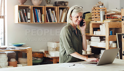 Buy stock photo Shot of a mature woman talking on a cellphone and using a laptop while working in a pottery studio