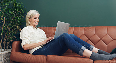 Buy stock photo Full length shot of an attractive mature woman sitting alone on her sofa and using her laptop at home