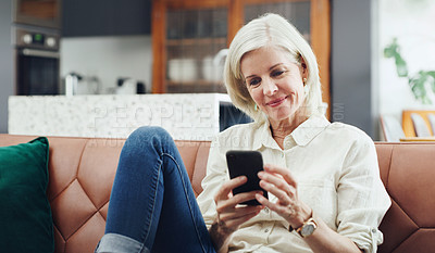 Buy stock photo Cropped shot of an attractive mature woman sitting alone on her sofa and using her cellphone at home