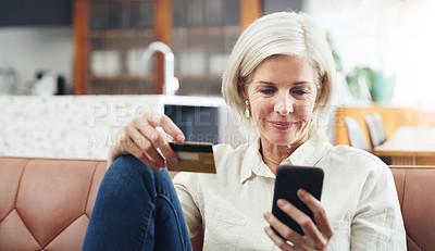Buy stock photo Cropped shot of an attractive mature woman sitting alone on her sofa and using her cellphone for online shopping