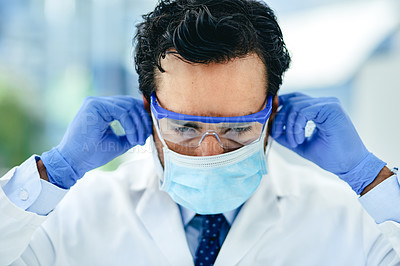 Buy stock photo Shot of a young scientist wearing protective glasses and a mask in a lab
