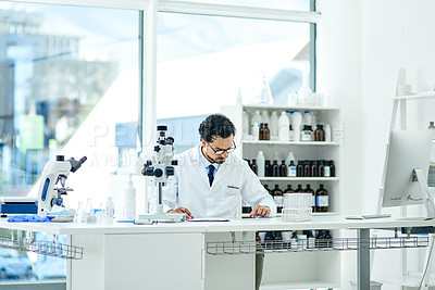 Buy stock photo Shot of a young scientist going through paperwork while using a digital tablet in a lab