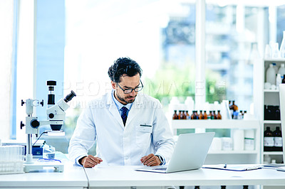 Buy stock photo Shot of a young scientist working on a laptop in a lab