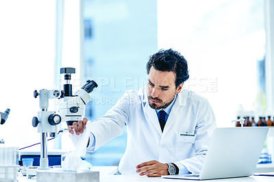 Buy stock photo Shot of a young scientist reaching for a tissue from a tissue box in a lab