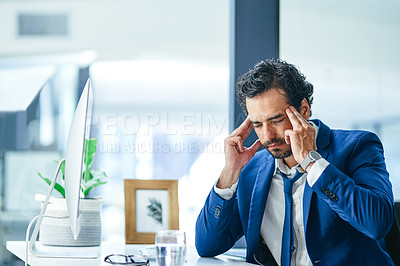 Buy stock photo Shot of a young businessman looking stressed out while working at his desk