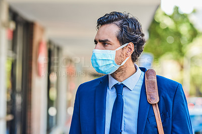 Buy stock photo Shot of a young businessman wearing a mask and walking through the city