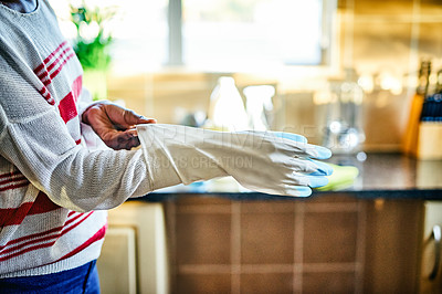 Buy stock photo Cropped shot of an unrecognizable woman putting on gloves before cleaning in her kitchen at home