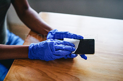 Buy stock photo Cropped shot of an unrecognizable woman cleaning the screen of her smartphone at home