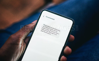 Buy stock photo Cropped shot of an unrecognizable woman reading a COVID-19 related text message on her smartphone at home