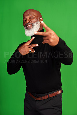 Buy stock photo Studio shot of a senior man showing peace signs while posing against a green background