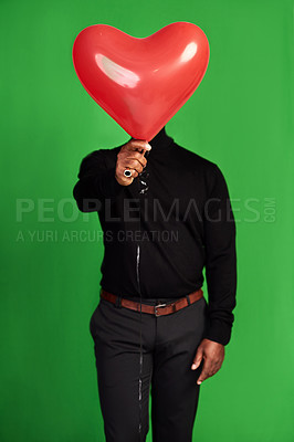 Buy stock photo Cropped shot of a man posing with a heart-shaped balloon in front of his face