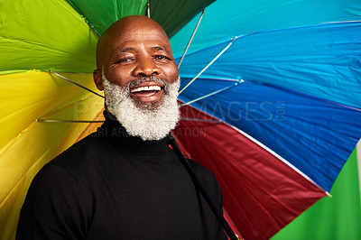 Buy stock photo Shot of a senior man posing with a colorful umbrella over his head